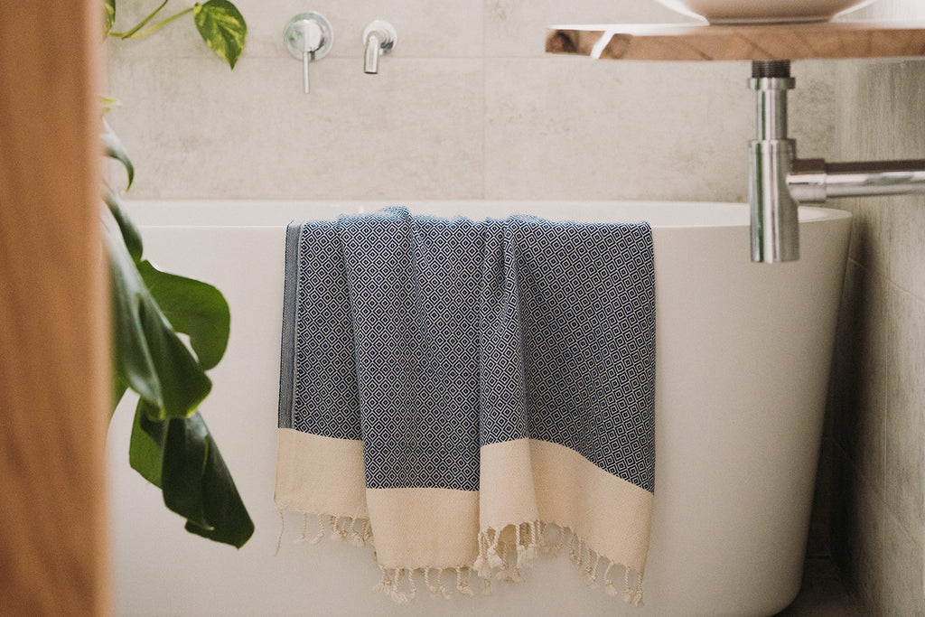 Arc Lore soft and lightweight organic cotton bath towel in the colour blue draped over a bathtube