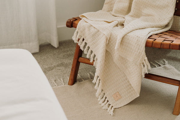 Linen blanket with a waffle design hanging over a modern leather armchair