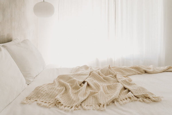 Oatmeal coloured waffle design linen bed throw in queen size spread on a bed in an airy and bright bedroom