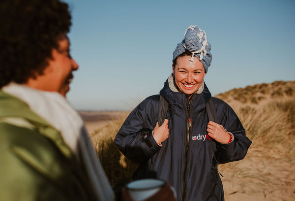 Two friends by the beach post swim with a hot drink and Arc Lore hair turban in the colour blue