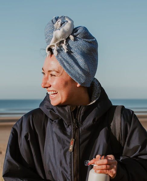 A swimmer post swimmer wrapped warm in a dry robe holding a flask of hot tea in her hands and laughing to her swim buddy. To fast dry her wet hair it is wrapped in turban style with an Arc Lore fast drying hair towel in the colour blue.