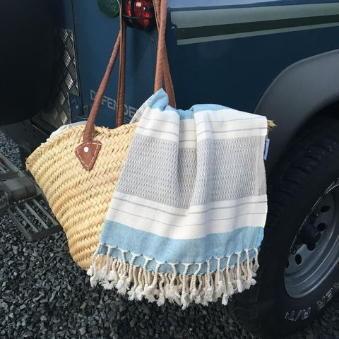 An organic cotton towel by Arc Lore hanging over a woven carry bag ready for an outdoor adventure