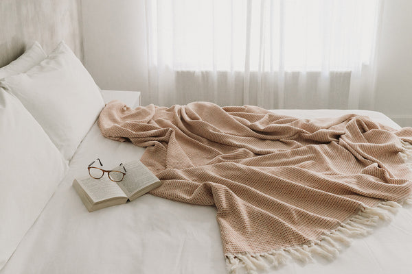 Arc Lore organic cotton blanket in terracotta scrunched up on the bed