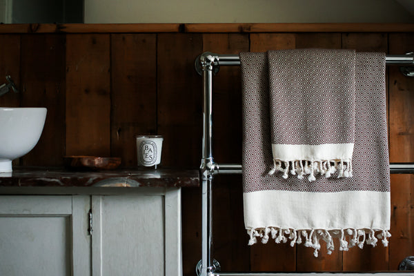 Matching hazelnut bath towels hanging on a bath rail in a wooden detailed bathroom with duck egg cabinets