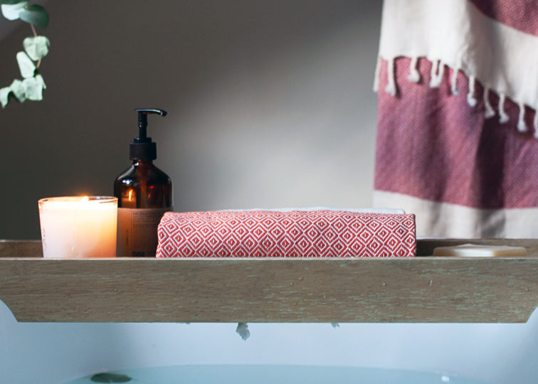 Organic cotton bath set in berry and burnt orange. Small organic towel rolled up on a bath tray rest over a hot bath infused with essential oils and candles