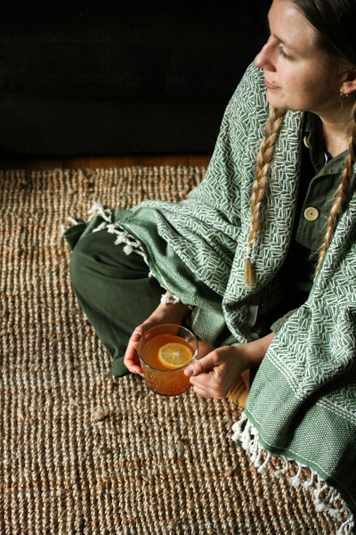 Sage green Arc Lore organic throw used as a shawl wrapped over a lady at home with a cup of lemon and honey tea. For home and travel. Size to suit the sofa or for use as a shawl.