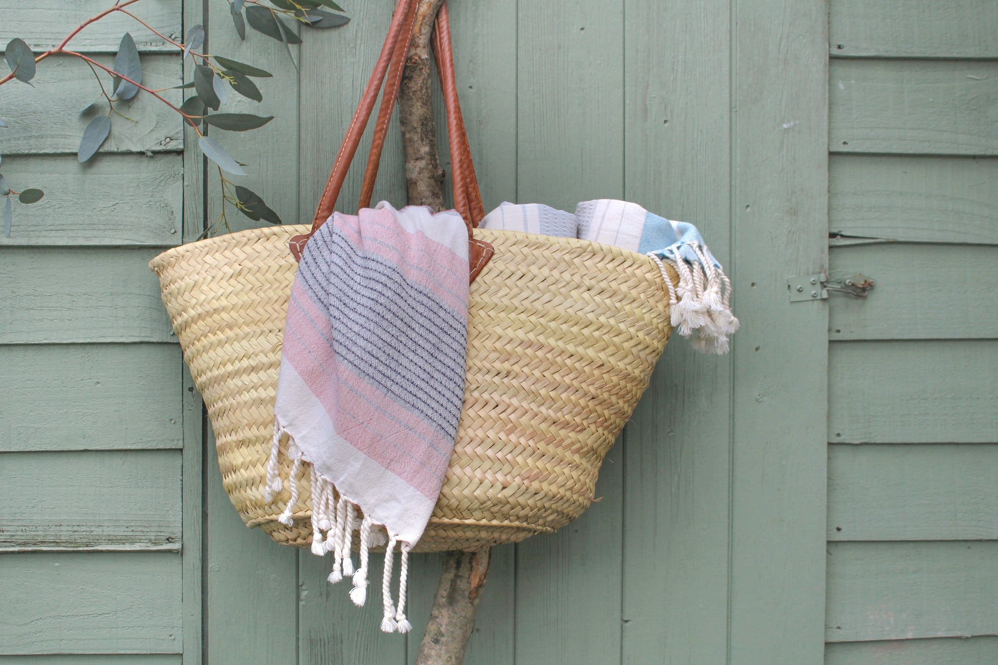 Hara organic cotton lightweight beach towel by Arc lore, packed in a woven straw bag hanging in front of a beach hut