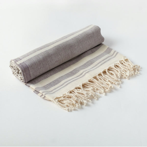 Arc Lore Mydo organic cotton beach towel in a mist colour with bold stripes rolled up.