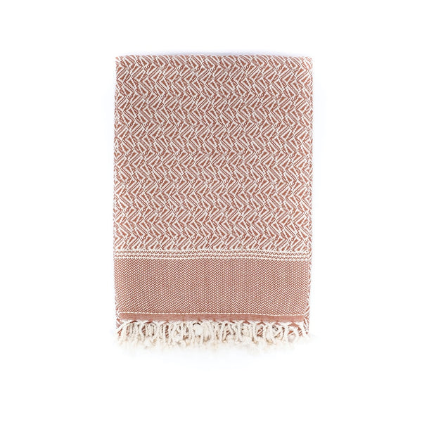Arc Lore Loku organic cotton travel blanket in the colour coco with woven triangular patterns.