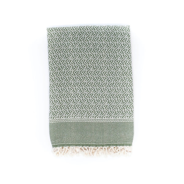 Arc Lore Loku organic cotton travel blanket in the sage green colour with woven triangular patterns.