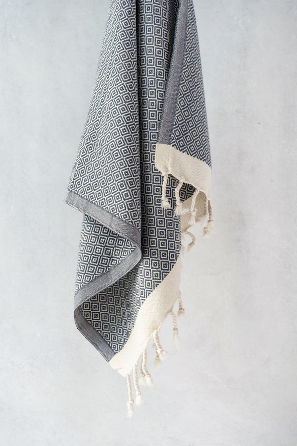 Arc Lore Samimi organic cotton hair towel in the colour charcoal shown hanging in a modern bathroom.