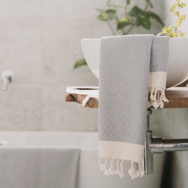 Arc Lore ultra soft organic cotton hand towel in the colour light grey with diamond patterns draping over a bathroom sink