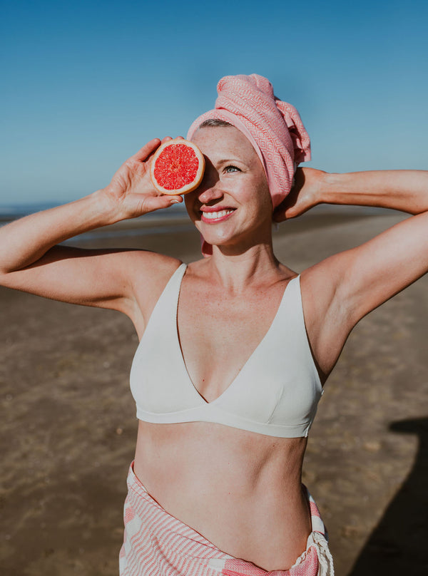 Stylised shoot of swimmer by the beach in a white bikini top with an Arc Lore beach towel wrapped as a sarong and a pink mini hair towel drying her hair as a turban