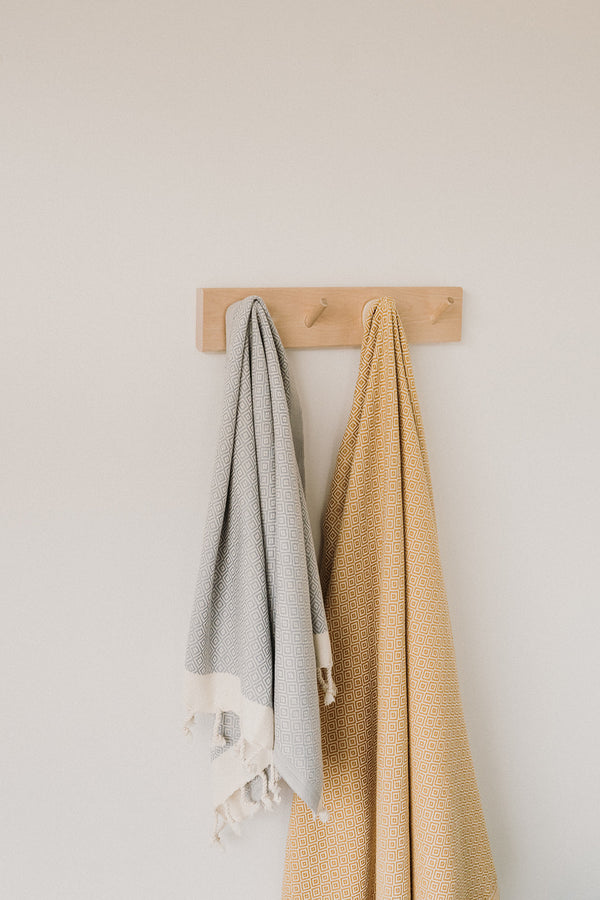 Arc Lore quick to dry organic cotton hand towel in the colour light grey hanging from a hook next to a large sized bath towel