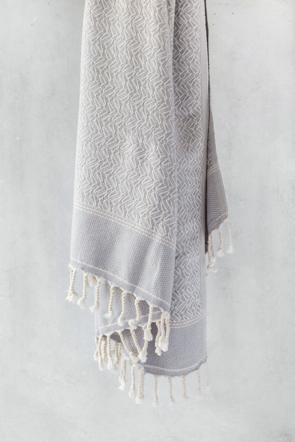 Loku organic cotton travel throw by Arc lore in grey colour with off white cross stitches