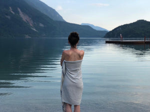 A swimmer by the edge of a lake in Italy wrapped in the Hara organic sports towel by Arc Lore featured in the two-toned colour blue mist with stripes