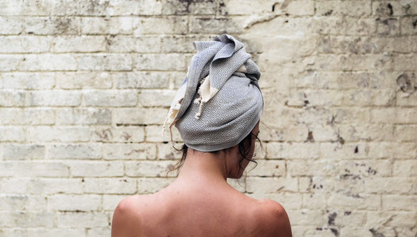 Woman just after an outdoor shower with hair wrapped in a Samimi Mini. Samimi mini organic hair towel is an ideal choice as a rapid hair drying towel. It soaks up water without leaving you drenched
