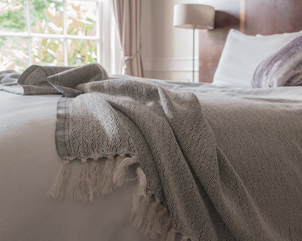 Ultra soft organic cotton bed throw in the colour cloud grey on a queen-sized bed. Natural cotton blanket