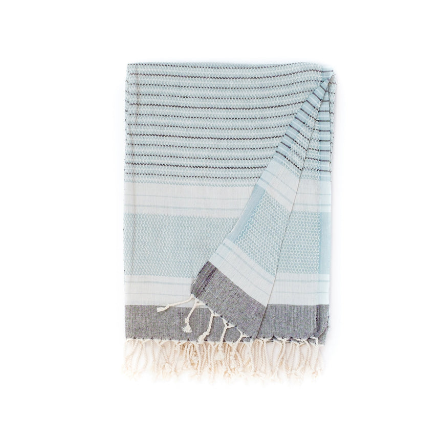 A lovely aquamarine-coloured Yalo organic active towel over the shoulders of a lady spending a day at the beach. Lightweight, absorbent and quick drying - all the qualities you would want in a towel but does not compromise on beauty and style.