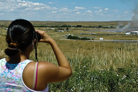 Sales and customer care rep Alyssa Janis investigates with a pair of binoculars. She said she keeps a pair in her car at all times.