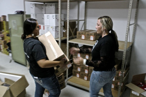 Kelly Hunter and Supply Chain Manager, Rachel Hunter, stock the warehouse shelves with new Tanka Bars.
