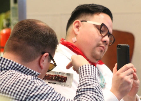 Daniel Yang, director of organizing and community building at Native American Community Development Institute holds the new Warrior Bar while Jay Bad Heart Bull of NACDI takes a photo with his phone. The views on the Warrior Bar were favorable.