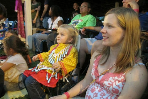 Charlotte with her mother Mandy sit in the shade arbor at the pow wow.