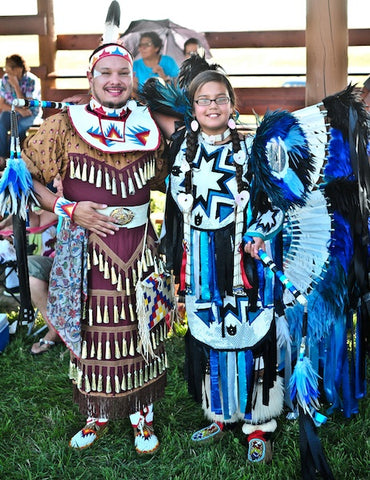 Corey Stover in a traditional jingle dress next to Emma Sioux Mann who is wearing his Men's Fancy regalia for the Switch Dance competitions. Corey won first place for his performance.
