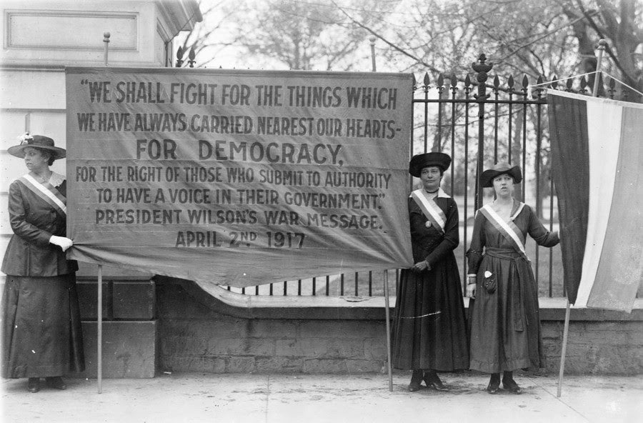 Three women carry banners for suffrage during a picket in front of the White House in Washington D.C. (Library of Congress