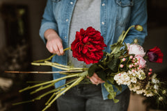 a florist from Thatch and Roses Flower Studio preparing a bouquet