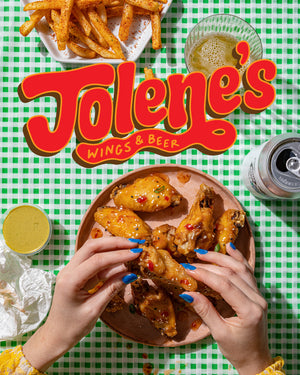 Jolene's Wings and Beer.  Image of hands holding chicken wings served with fries and beer.