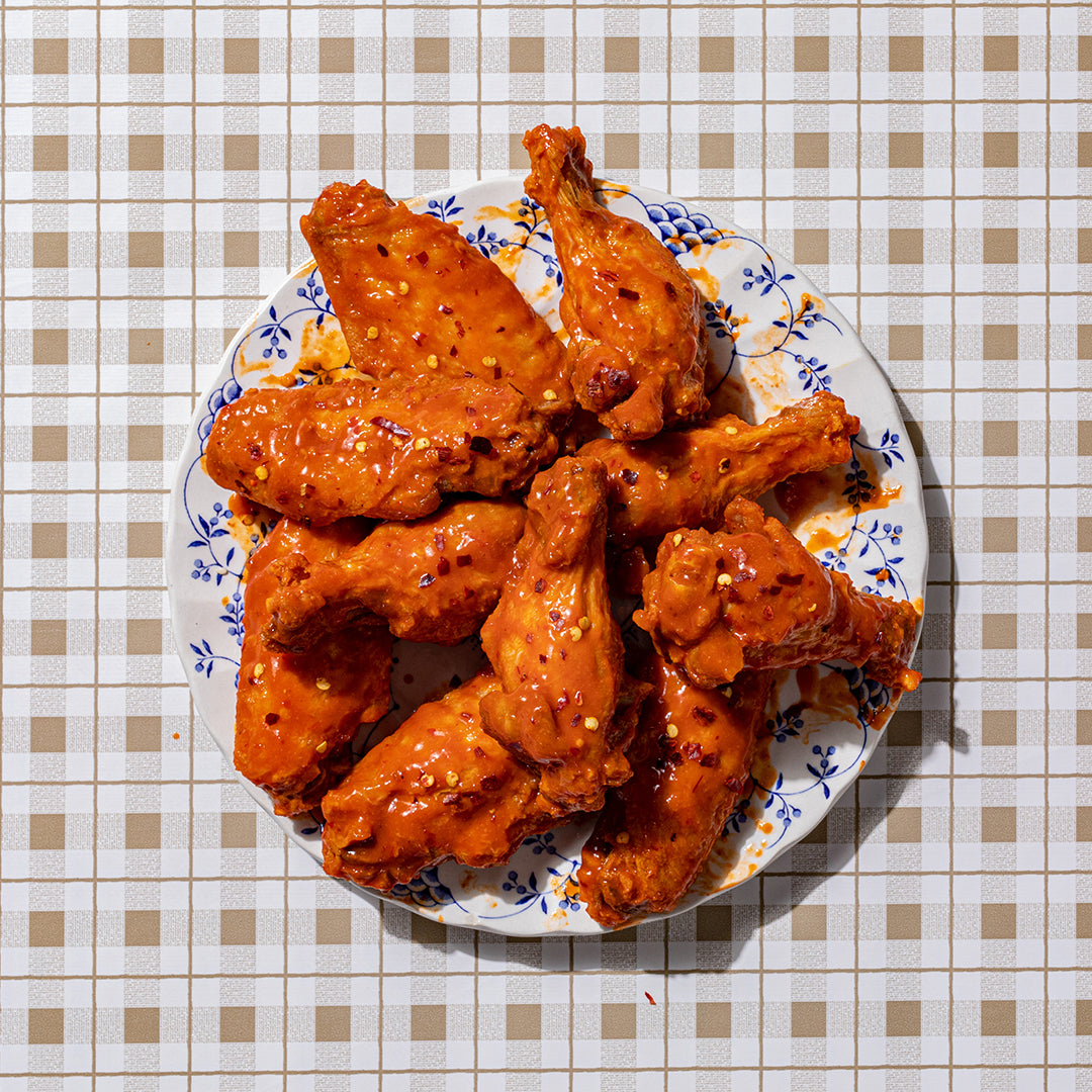 A plate of Nashville Hot Wings - the definition of mouthwatering, our hottest style wing packing some real fire balanced with the perfect touch of tangy vinegar goodness. Available boneless or bone in