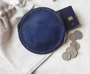 Navy round purse flat lay with art illustration