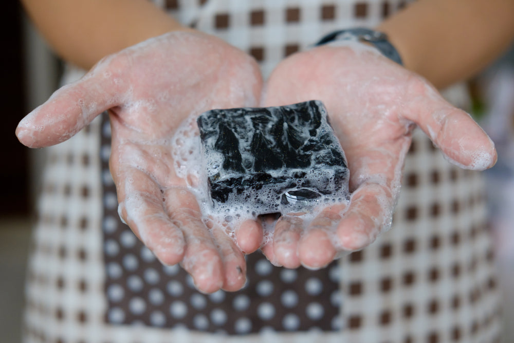 Activated charcoal soap Woman washing her hands with black handmade soap Runoku all natural soap