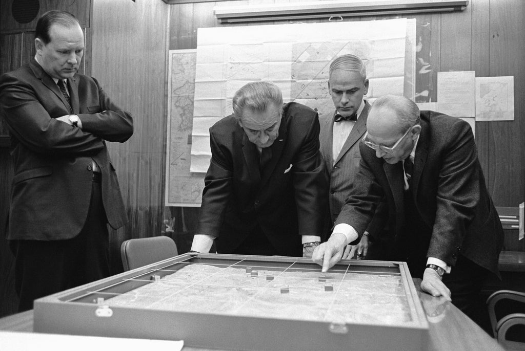 President Lyndon B. Johnson studies a scale a model of the Khe Sanh area, 15 February 1968