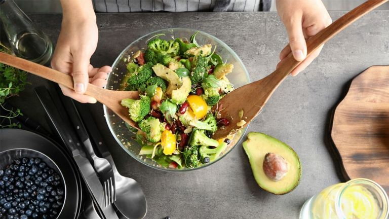 hands holding wooden ladle mixing avocado and green leafy veggie salad in a glass bowl