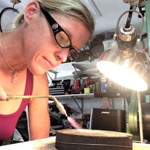 Load image into Gallery viewer, Sarah Miller artist at bench using torch Seaside Harmony Jewelry