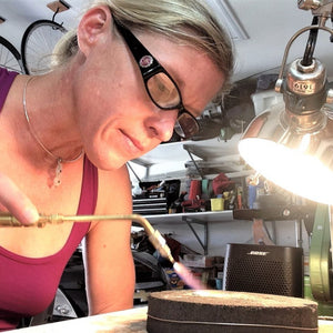 Sarah Miller artist at bench using torch Seaside Harmony Jewelry