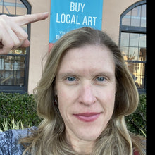 Load image into Gallery viewer, Sarah Miller artist in front of buy local art sign