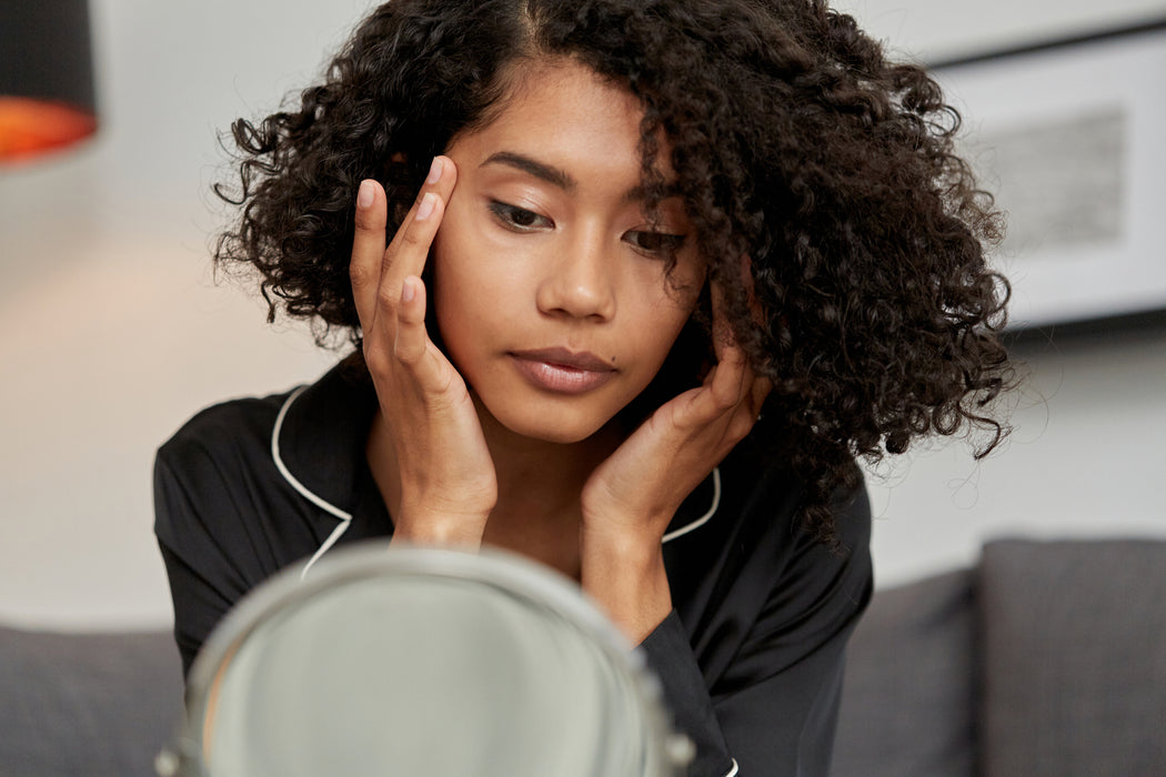Young woman applying Kym Nylz Castor Oil to her temples while looking in the mirror. Her natural, curly, chin length hair is down, and she's wearing black pajamas.