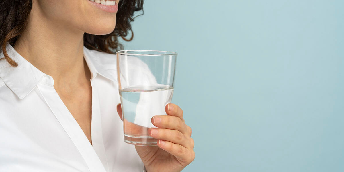 Woman holding drinking water glass in her hand