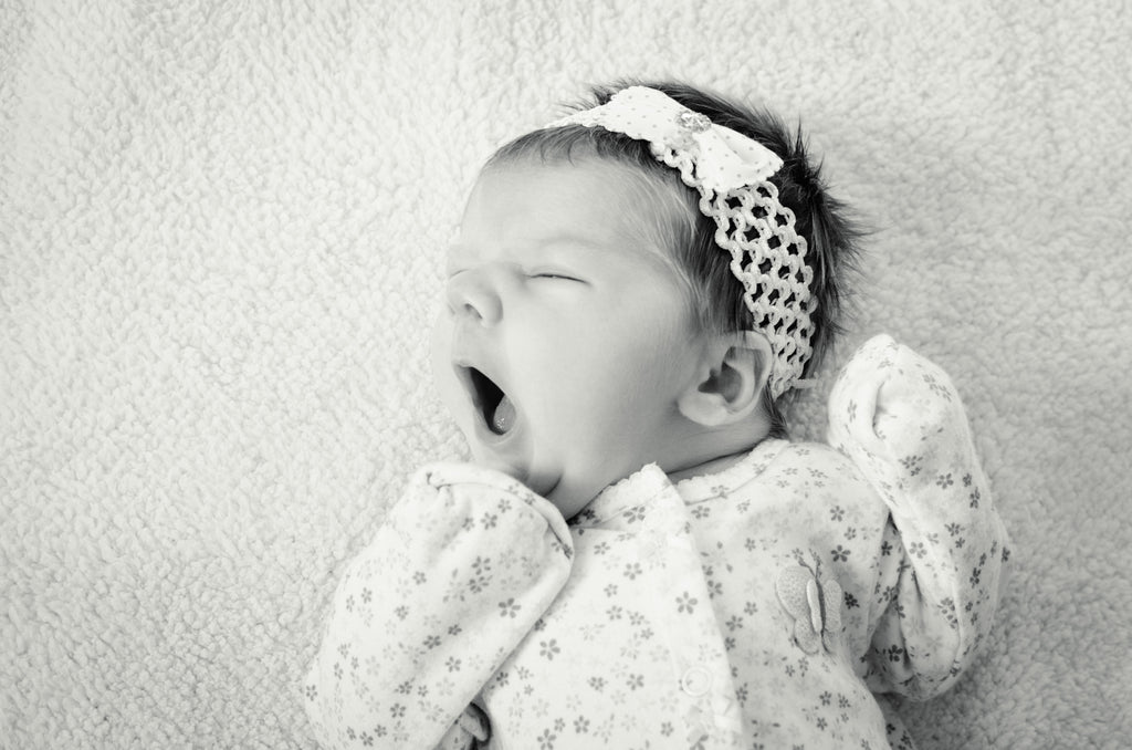 Baby infant yawning in her pajamas and headband bow