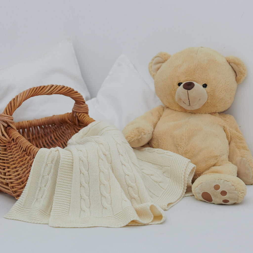 Teddy bear next to a basket with a swaddle blanket
