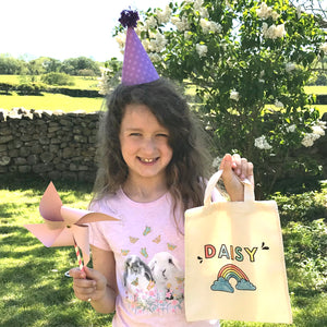 Birthday girl with a party hat, personalised canvas bag and a paper pinwheel
