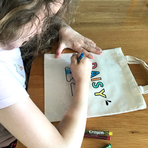 Little girl colouring in a personalised canvas bag with her name and a rainbow on it.