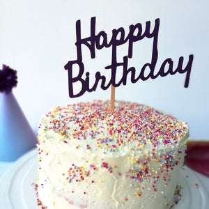 A birthday cake full of sprinkles with a Happy Birthday cake topper in the top and a paper party hat in the background.