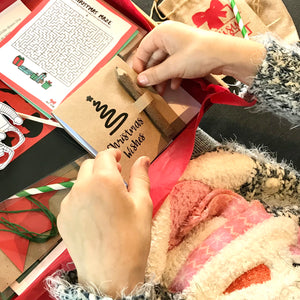 A child looking through a letterbox full of Christmas craft, games and activities