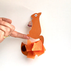 Red squirrel balancing craft, balancing on a finger.