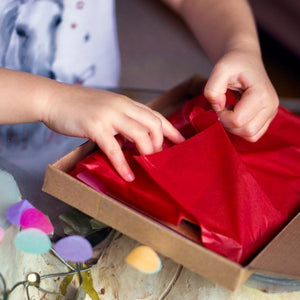 Child opening an activity pack, beautifully wrapped in tissue paper.