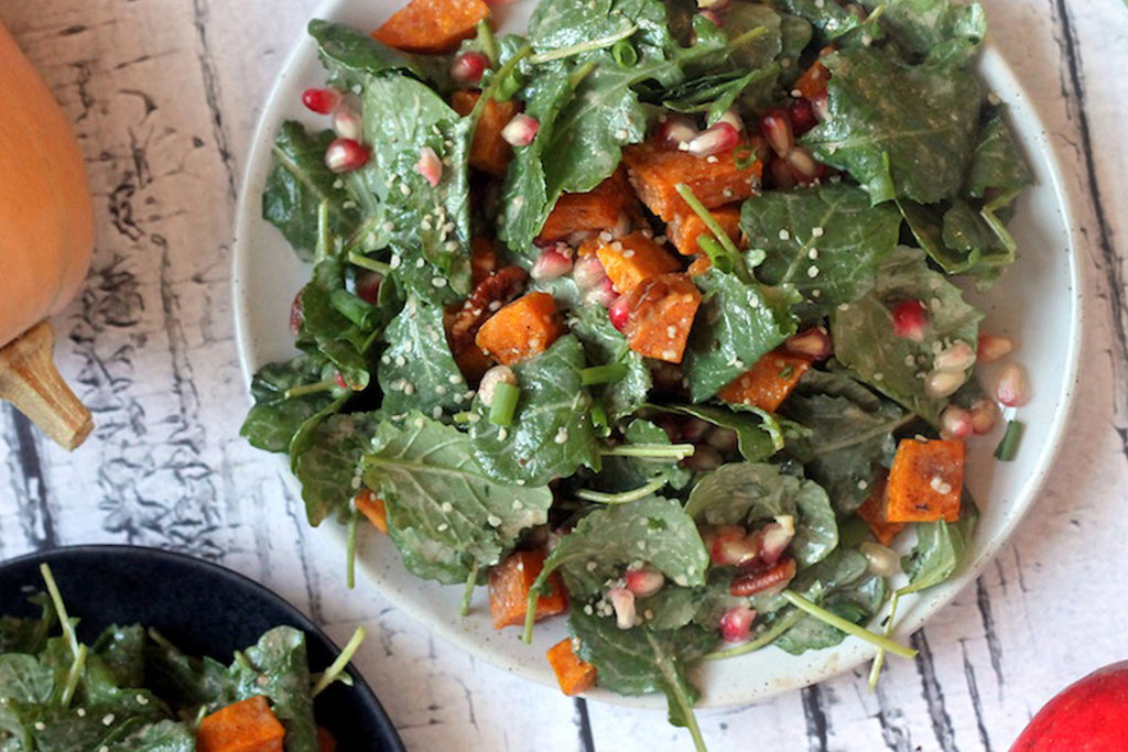 Fall Superfood salad featuring ingredients such as spinach, butternut squash, pomegranate seeds, hemp hearts, and red onion on a plate next to fall produce
